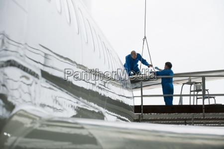 engineers assembling tail of passenger jet
