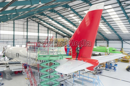 engineers inspecting tail of passenger jet