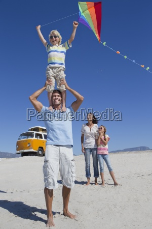 happy family flying kite on sunny