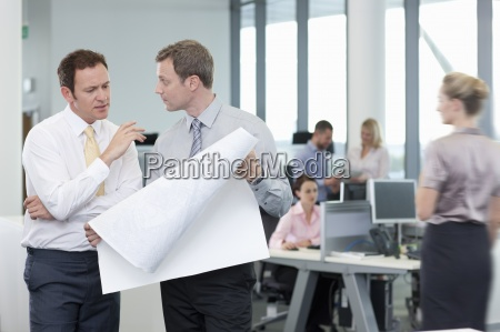 architects reviewing blueprints in office