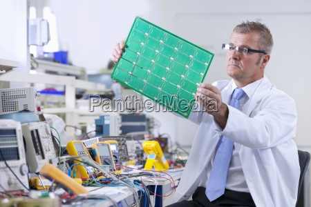 engineer examining printed circuit board at
