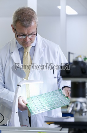 engineer examining circuit board under magnification