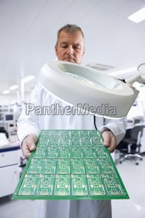 engineer examining circuit board under magnifying