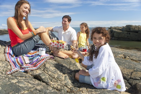 happy family picnicking on rocks along