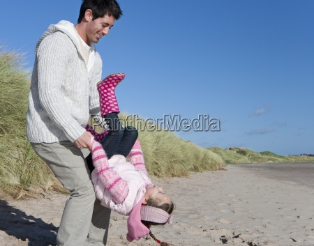 father holding daughter upside down on