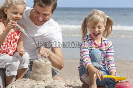 father and daughters making sandcastle on