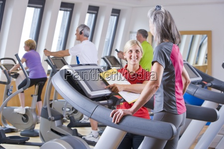personal trainer guiding woman on treadmill