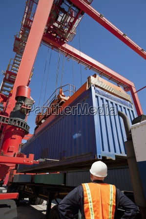 worker watching crane load cargo container