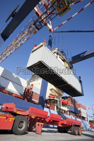 crane unloading container ship at commercial