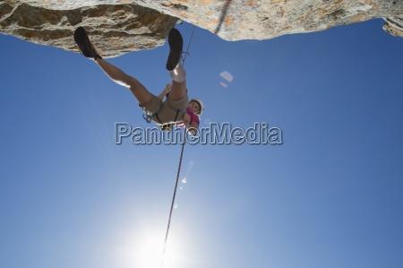 sun shining above female rock climber