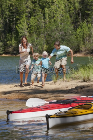 family running toward kayaks at lakeside