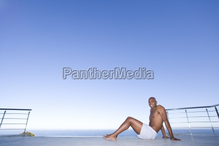 young man sitting on ground by