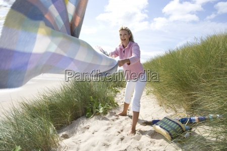 young woman holding blanket at beach