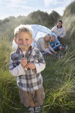 young family camping boy holding sausage