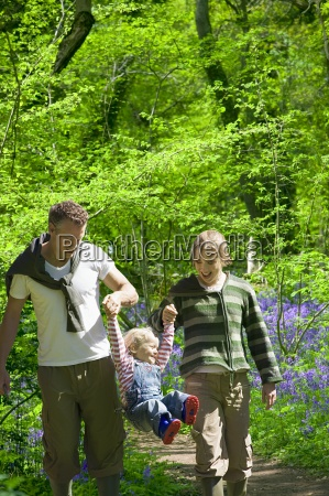 couple swinging child in forest with
