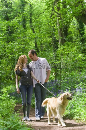 couple and dog walking in forest