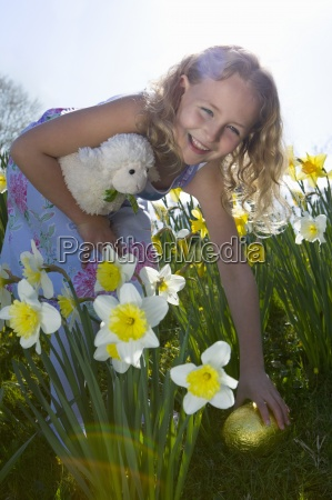 girl finding chocolate easter eggs in