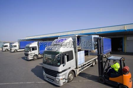 worker driving forklift loading semi truck