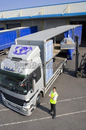 worker near forklift loading semi truck