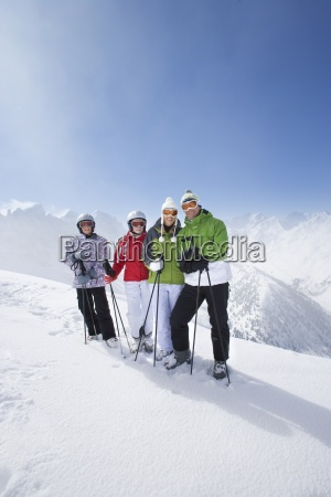 family of skiers smiling together on