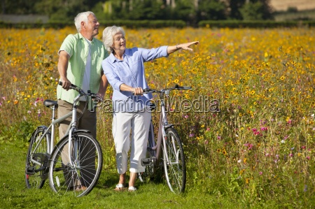 couple with bicycles pointing among wildflowers