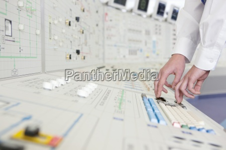 engineer pushing buttons on panel in