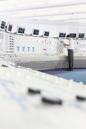 engineer with binder at control panel