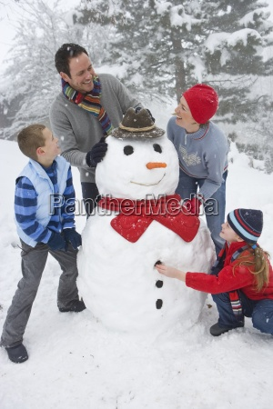 family building snowman in snow