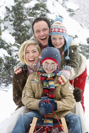 portrait of happy family on snowsled