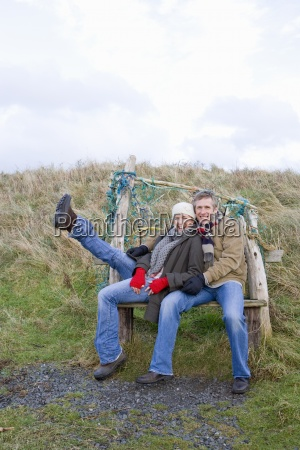 couple sitting on bench enjoying outdoors