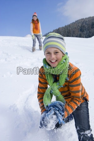 brother and sister having snowball fight