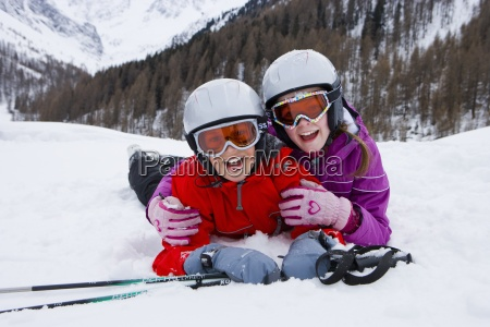 brother and sister skiers laying in