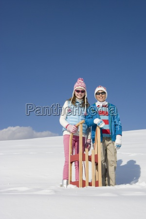brother and sister standing in snow