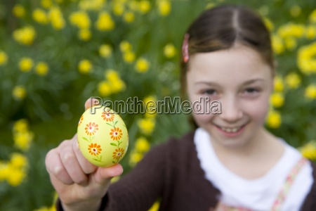 young girl holding decorated easter egg