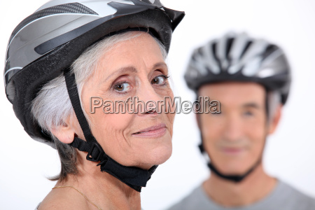 older couple wearing cycling helmets