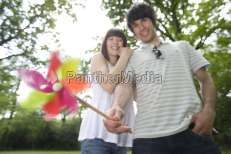 young couple outdoors man with pinwheel