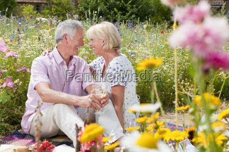 smiling senior couple drinking wine and