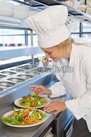 zuversichtlich laechelnde koch bereitet salat platten