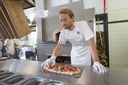 smiling kuechenchef bereitet pizza in der