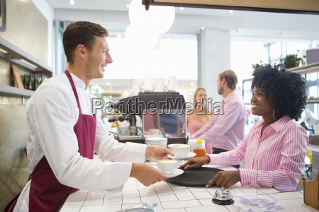 smiling waiter and waitress serving coffee