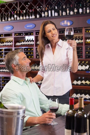 curious couple examining glass of red