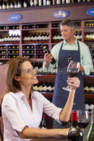 curious woman examining glass of red
