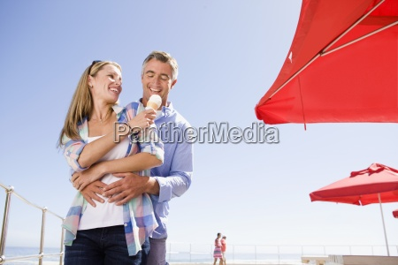 smiling couple sharing ice cream at