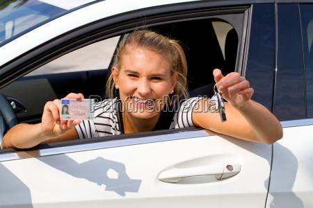 junge frau im auto mit fuehrerschein