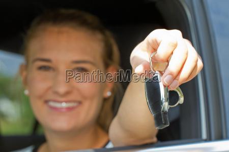 junge autofahrerin mit schluessel in der