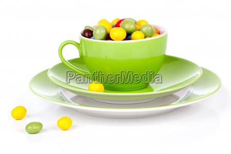 gruene tasse mit bunten suessigkeiten
