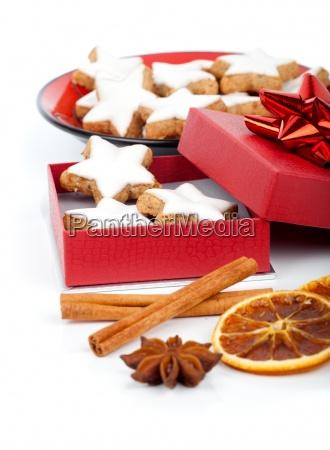 weihnachtsplaetzchen im roten geschenkbox mit weihnachtsdekorati