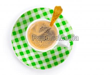 gruene tasse kaffee mit goldenen loeffel