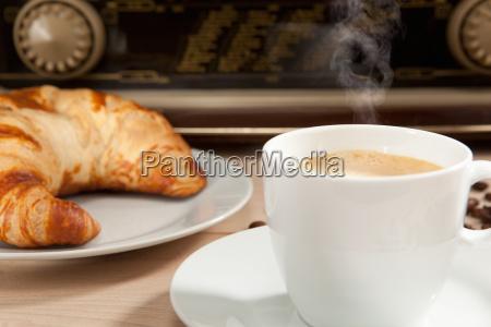 radiohoeren beim fruehstueckskaffee mit croissant