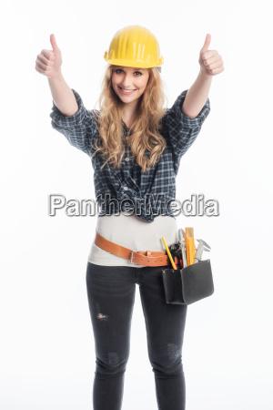 weiblicher handwerker mit werkzeug zeigt daumen
